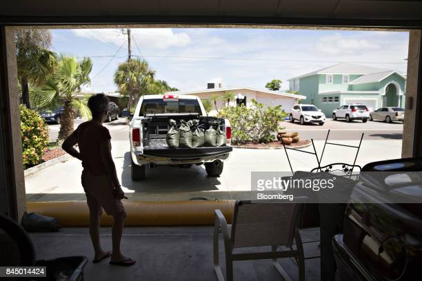 A woman looks at a pickup truck filled with sandbags from her garage as she and her husband prepare ahead of Hurricane Irma in Redington Beach...