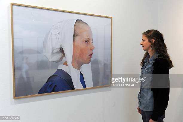 A woman looks at a picture by French photographer Charles Freger during an exhibition on traditional costumes and headdresses in Brittany on June 20...