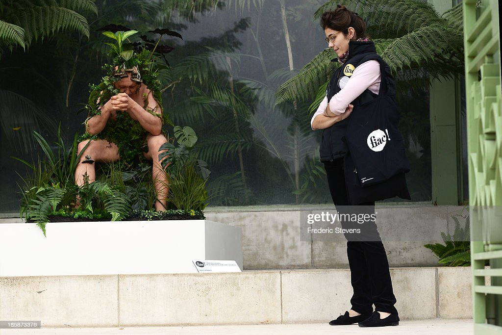 A woman looks at a piece by French artist Gilles Barbier entitled 'Man still' at the Jardin des Plantes as part of the outdoor exhibition of the FIAC International Contemporary Art Fair on October 25, 2013 in Paris, France. This is the 40th anniversary edition of