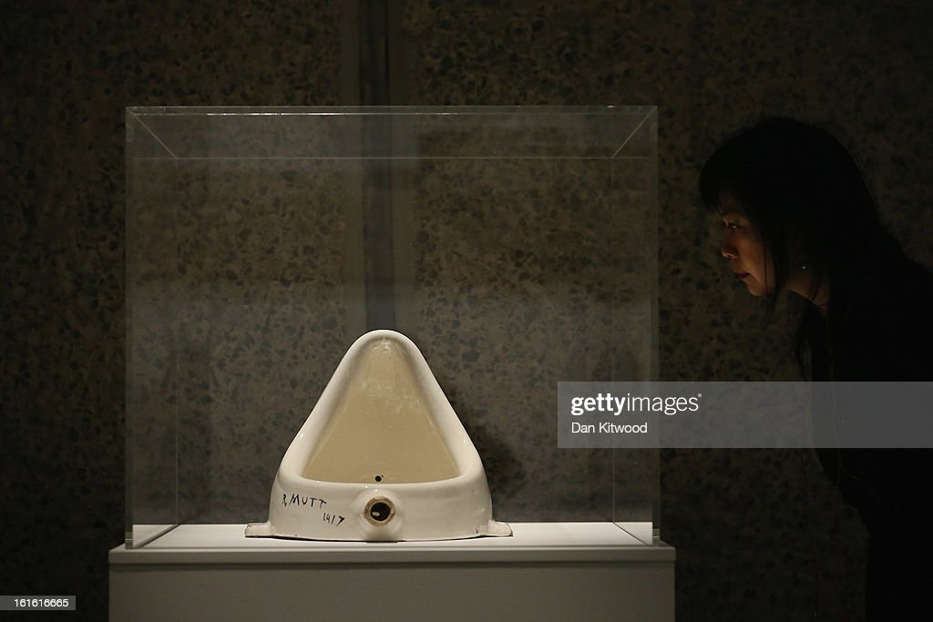 A woman looks at a piece of work entitled 'Fountain' by Marcel Duchamp during a press preview of 'The Bride and the Bachelors' exhibition at the...