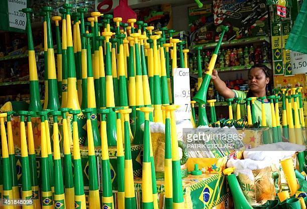 A woman looks at a plastic horn in the Brazilian colours at a shop in Belo Horizonte on July 8 2014 prior to the start of the 2014 FIFA World Cup...