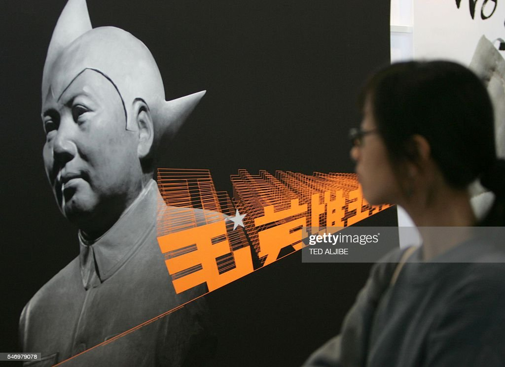 A woman looks at a portrait of futuristic rendition of late Chinese leader Mao Zedong displayed at the design and Innovation exhibition as part of...