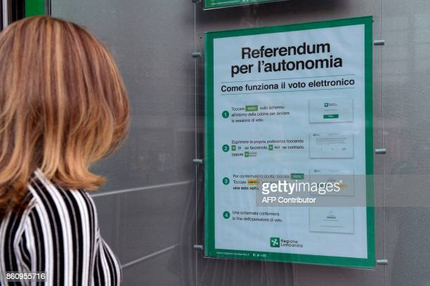 A woman looks at a poster explaining how to vote for a referendum in Italy's northern region of Lombardy to request more autonomy from central...