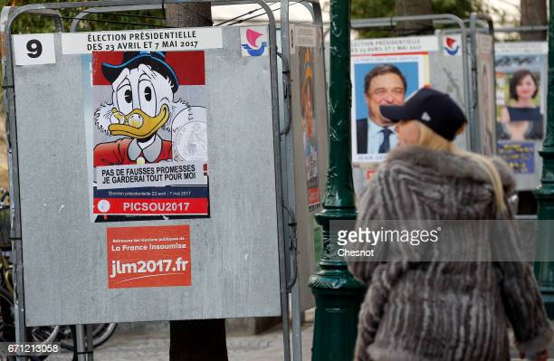 A woman looks at a poster with the Disney character Uncle Scrooge fixed over the official poster of French presidential election candidate for the...
