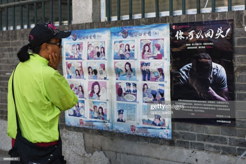 A woman looks at a propaganda cartoon warning local residents about foreign spies, in an alley in Beijing on May 23, 2017. The cartoon is a graphic reminder of a struggle most often waged in the shadows, and a sign of the Chinese government's intensifying campaign against espionage.