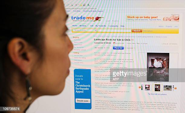 A woman looks at a screen showing the 'Trade Me' auction interet offering a rock from the Christchurch New Zealand earthquake for sale in Hong Kong...