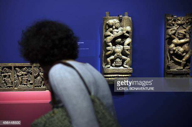 A woman looks at a sculpture as she visits the exhibition The KamaSutra spirituality and erotism in Indian art at the Paris' pinacotheque on October...