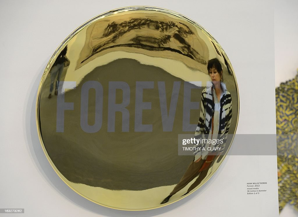 A woman looks at a sculpture by Hank Willis Thomas titled 'Forever' during the press preview at the 2013 Armory Show, one of the world's top art events featuring the most influential artworks of the 20th and 21st centuries, at Pier 92 and 94 in New York March 6, 2013. The Armory Show Centennial Edition kicks off Armory Arts Week .