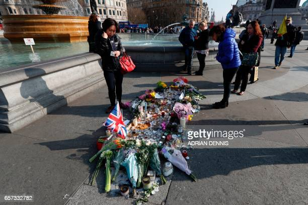 A woman looks at a small memorial and floral tributes to the victims of the March 22 terror attack on the British Parliament and Westminster Bridge...