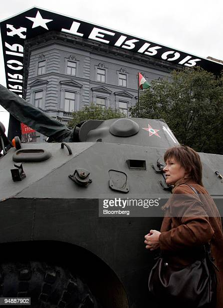 A woman looks at a Sovietera tank placed in front of the Terror Museum as part of programs marking the 50th anniversary of the 1956 antiSoviet...
