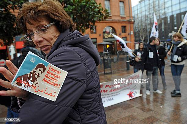 A woman looks at a sticker reading 'Free Georges Ibrahim Abdallh' a propalestinian militant during a protest in Toulouse southwestern France on...