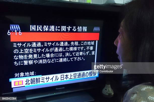A woman looks at a television news displaying warnings via the 'Jalert' system in Tokyo on August 29 following a North Korean missile test that...