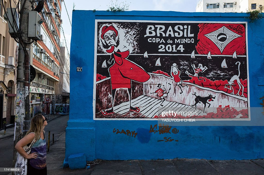 A woman looks at a wall painted by Chilean-born Brazilian painter Jorge Selaron on the FIFA World Cup Brazil 2014 in Rio de Janeiro, Brazil on July 21, 2013. Selaron was found dead past January 30 on the 'Escadaria Selaron', the stairs leading up to the Convent of Santa Teresa, which he decorated.