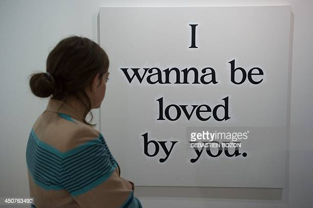 A woman looks at a work of art by US artist Ricci Albenda called 'I Wanna Be Loved By You' on June 17 2014 during the preview day of the Art Basel...
