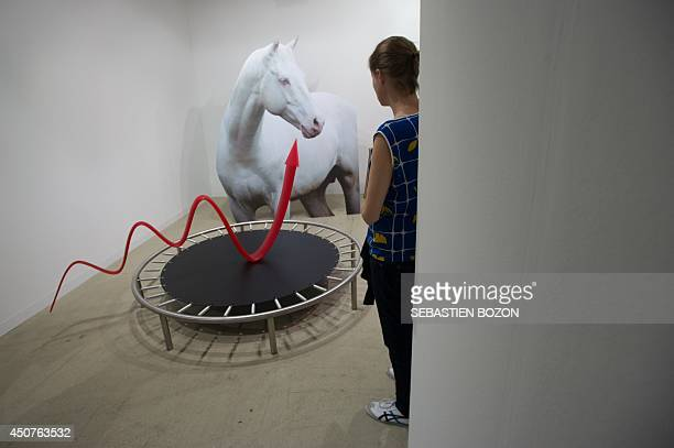 A woman looks at a work of art of Estonian artist Amsterdam based Katja Novitskova called 'Pattern of Activation' on June 17 2014 during the preview...