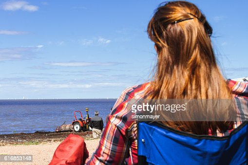 Woman looks at a ziphiid aground off the coast : Stock Photo