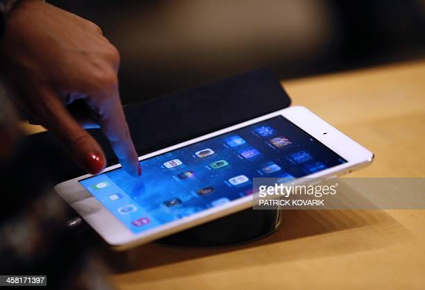 A woman looks at an Apple iPad at one of the company's stores in Paris on December 20 2013 AFP PHOTO / PATRICK KOVARIK