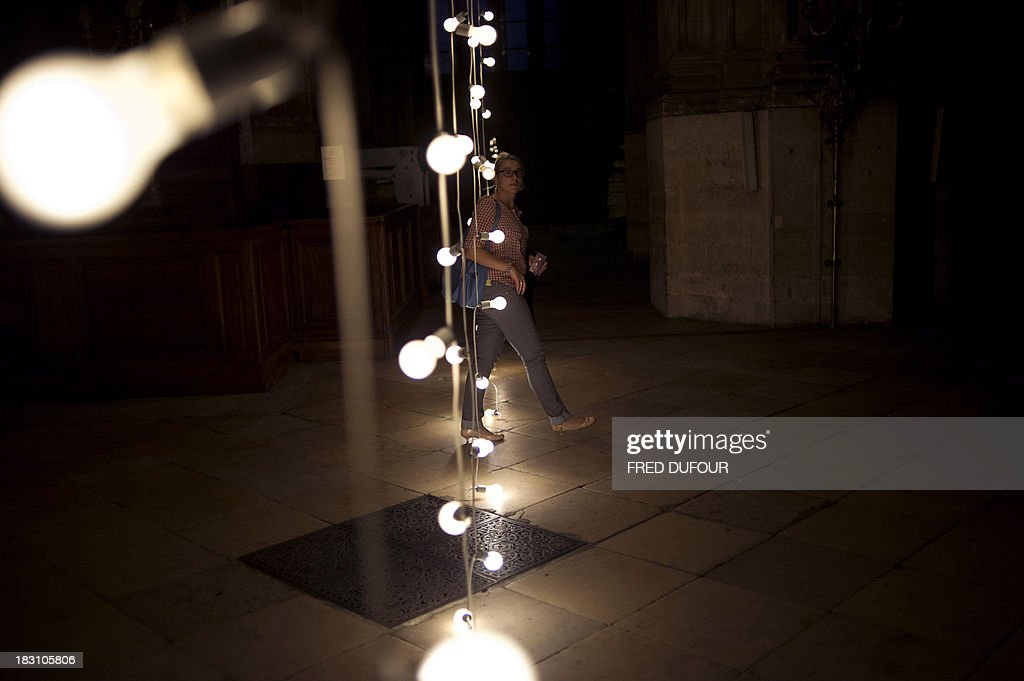 A woman looks at an art installation by artist Felix Gonzales-Torres on October 4, 2013, at the Saint Eustache church in Paris, on the eve of Paris' Nuit Blanche (White Night) event.