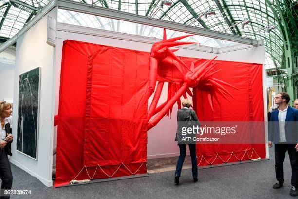 A woman looks at an artwork as she visits the Paris International Contemporary Art Fair at the Grand Palais in Paris during the press opening on...
