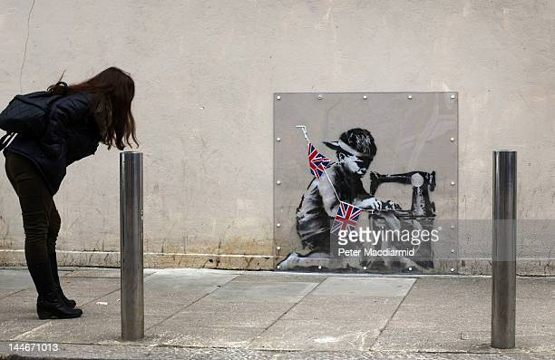 A woman looks at an artwork attributed to Banksy under a plastic cover on May 17 2012 in London England The stencilled image depicts a poor child...