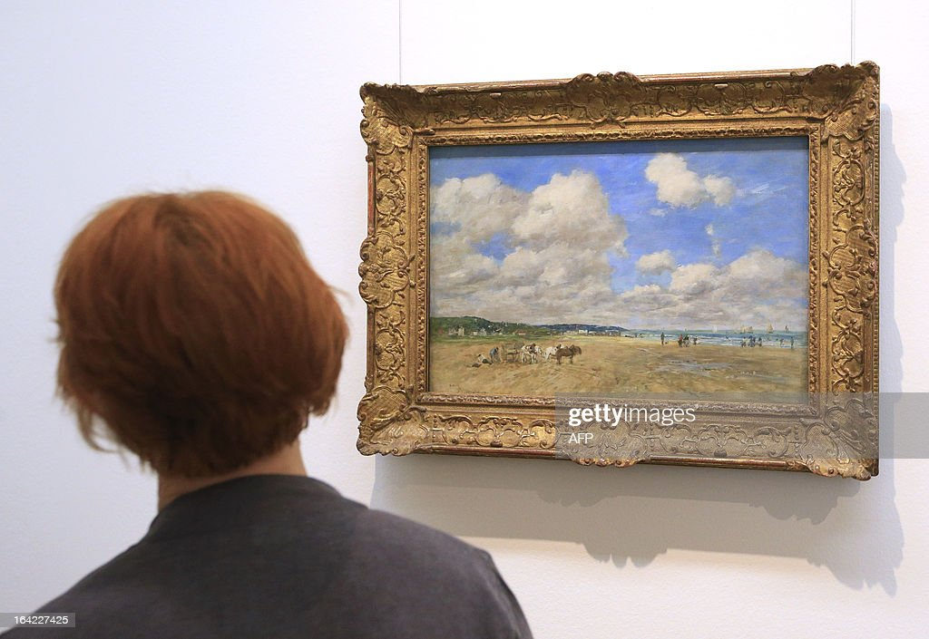 A woman looks at an artwork creation by French artist Eugene Louis Boudin, titled 'Deauville', dated 1893, as part of the 'Clouds' (Wolken) exhibition at the Leopold Museum in Vienna, on March 21, 2013. The exhibition will run until July 1, 2013.