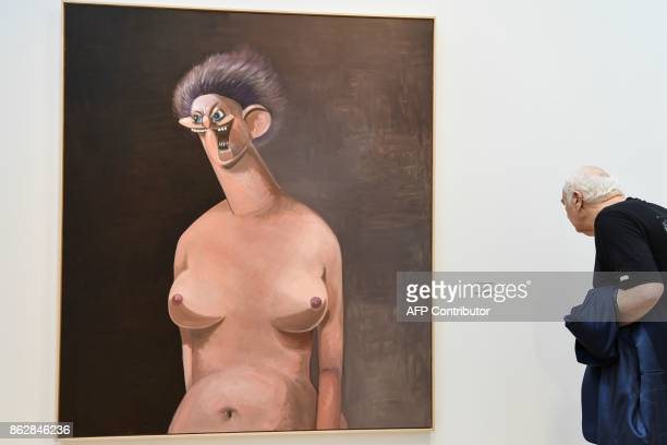 A woman looks at an artwork untitled 'Nude with purple hair 2010' by US painter George Condo as she visits the Paris International Contemporary Art...