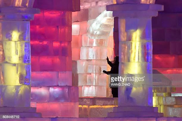 A woman looks at an ice sculpture at the China Ice and Snow World during the Harbin International Ice and Snow Festival in Harbin northeast China's...
