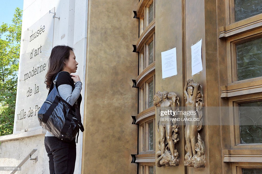 A woman looks at an information note on the door of the Paris' Musee d'Art Moderne (Paris modern art museum), closed on May 20, 2010 after five works including paintings by modern masters Henri Matisse and Pablo Picasso have been stolen. The canvases, worth a total of 500 million euros (635 million dollars), were discovered missing from the city-run Musee d'Art Moderne when it opened its doors.