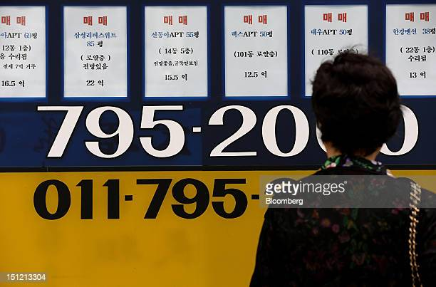 A woman looks at apartment prices displayed outside a real estate agency in Seoul South Korea on Tuesday Sept 4 2012 Seoul's metropolitan area with a...