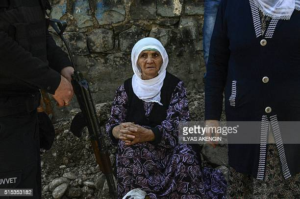 TOPSHOT A woman looks at armed police officer as they wait to enter their district after clashes ended in the Sur district of Diyarbakir on March 13...