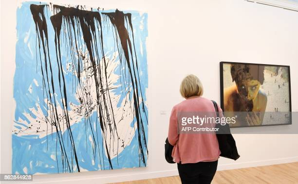 A woman looks at artworks as she visits the Paris International Contemporary Art Fair at the Grand Palais in Paris during the press opening on...