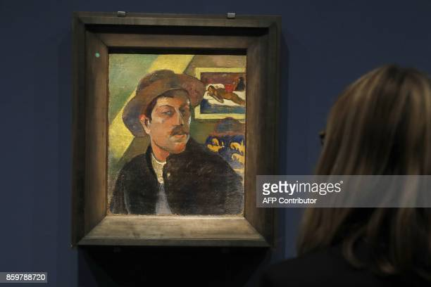 A woman looks at 'Autoportrait au chapeau' during the press visit to the exhibition of paintings by the French postImpressionist artist Eugène Henri...