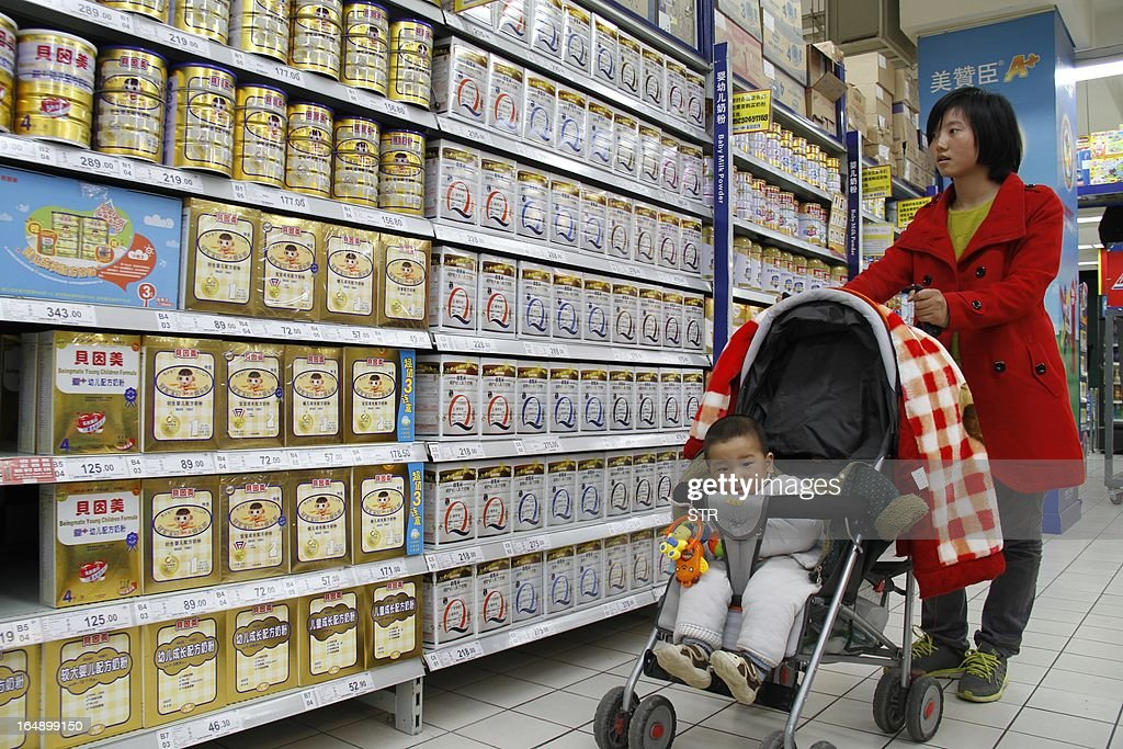 A woman looks at baby milk powder in a supermarket in Nanjing, east China's Jiangsu province on March 29, 2013. The Chinese partner of Hero Group, a major Swiss baby formula manufacturer, has been accused of deliberately mislabelling milk powder and a senior employee has been detained, officials said on March 26, 2013. CHINA OUT AFP PHOTO