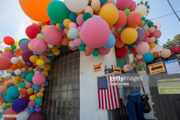 A woman looks at balloons covering a polling place at the Hollywood Sunset Free Clinic as Angelenos go to the polls on March 7 2017 in the Silverlake...