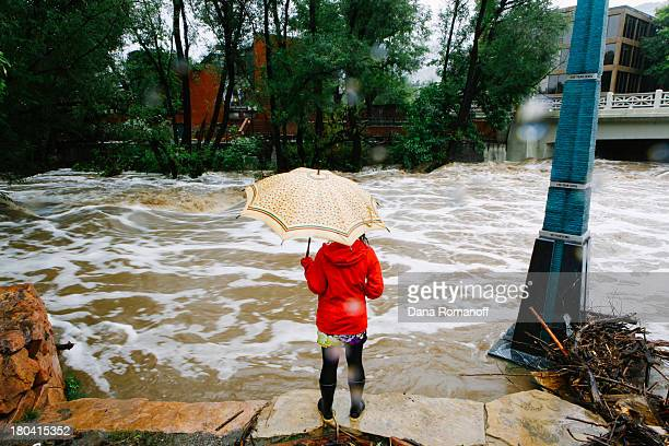 A woman looks at Boulder Creek which flooded early today after three days of heavy rainfall September 12 2013 in Boulder Colorado An estimated 610...