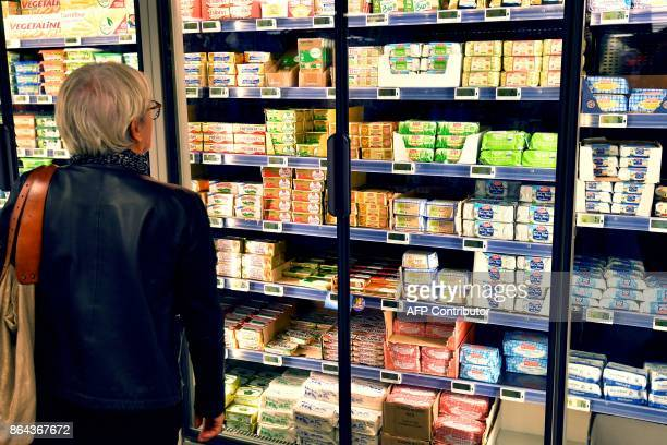 A woman looks at butter packages on refrigerated supermarket shelves on October 20 2017 in Nantes western France 'Due to a shortage of French milk...