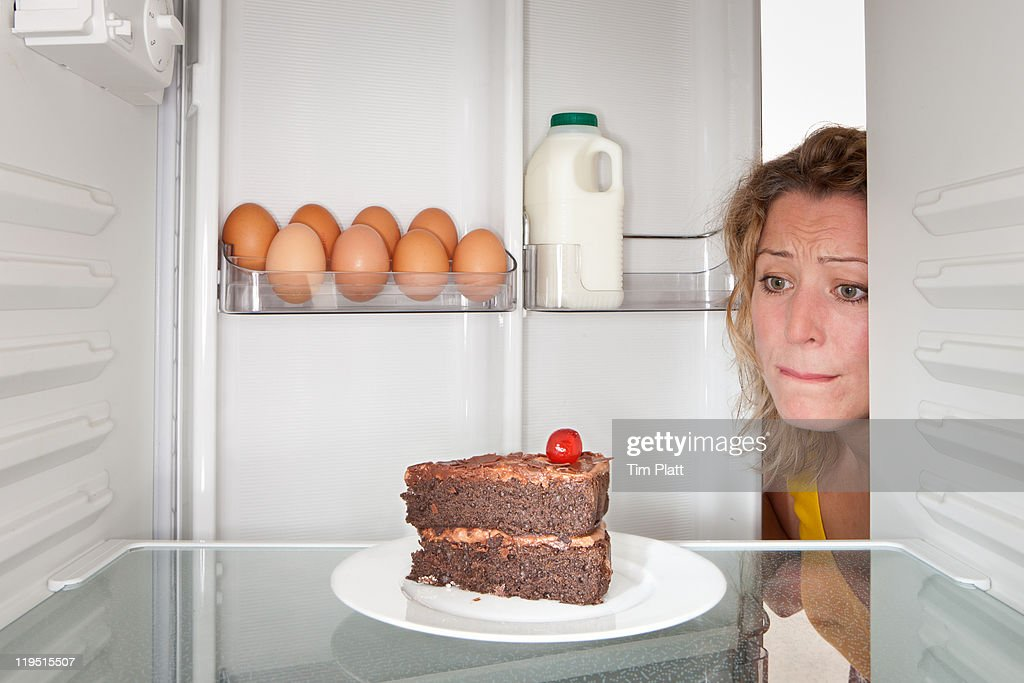 Woman looks at cake in a fridge. : Stock Photo