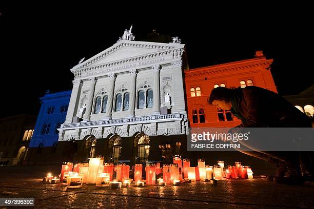 A woman looks at candles in front of the Swiss House of Parliament illuminated with the colours of the French national flag on November 16 2015 in...