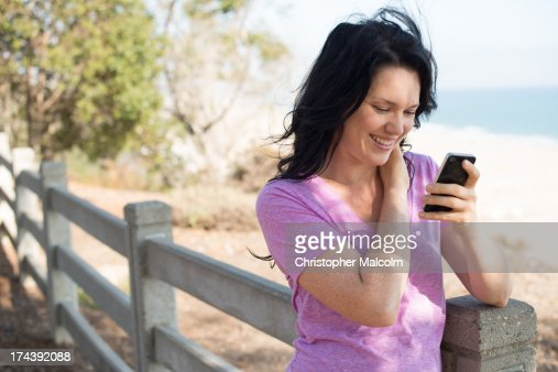 Woman looks at cell phone : Stock Photo