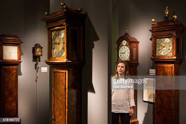 A woman looks at clocks for sale in the Tom Scott collection at the Masterpiece Fair on June 23 2015 in London England The Masterpiece Fair will be...