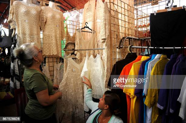 A woman looks at clothes at a market in Havana on October 27 2017 Almost drowned by the crisis of the 90s the emerging Cuban fashion begins to thrive...
