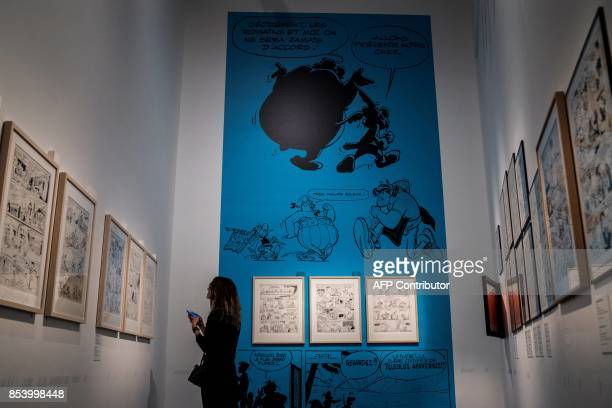 A woman looks at comic strips displayed during a preview of an exhibition dedicated to the work of French comics editor and scriptwriter Rene...