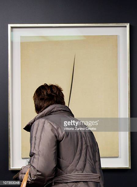A woman looks at 'Concetto Spaziale Attesa' by Lucio Fontana during the Museo Del Novecento Opening on December 6 2010 in Milan Italy