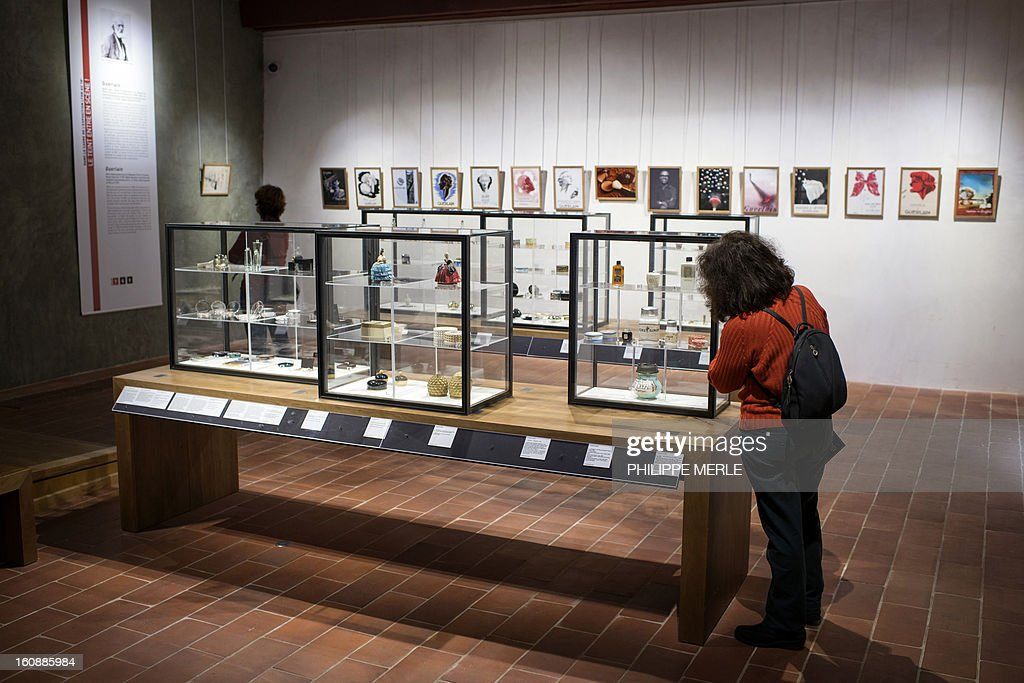 A woman looks at containers of cosmectics displayed on February 7, 2013 at the Gadagne Museum in the central french city of Lyon. After Hong Kong, Lyon opened on February 7 an exhibition of more than 200 rare pieces of beauty and makeup products: from 17th century boxes of beauty spots and whitening powders to sophisticated contemporary blush boxes, reflecting the evolution of women's makeup. AFP PHOTO / PHILIPPE MERLE