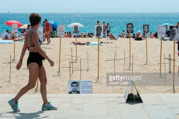 A woman looks at crosses and photographs of a dead migrants and refugees on Barcelona's Bogatell beach during an action called by pro human rights...