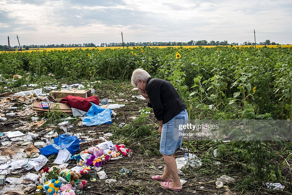 A woman looks at debris from Malaysia Airlines flight MH 17 which landed in a field of sunflowers on July 19, 2014 in Rassipnoye, Ukraine. Malaysia Airlines flight MH17 was travelling from Amsterdam to Kuala Lumpur when it crashed killing all 298 on board including 80 children. The aircraft was allegedly shot down by a missile and investigations continue over the perpetrators of the attack.