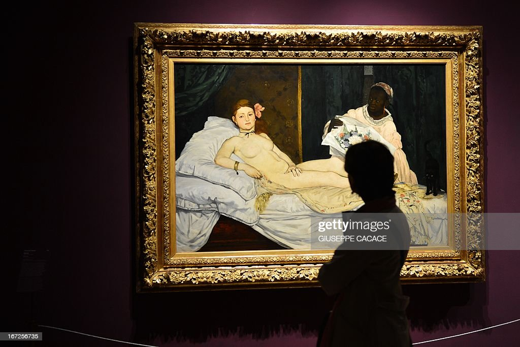 A woman looks at Edouard Manet's 'Olympia' on April 23, 2013 in Venice, during the 'Manet Return to Venice' exhibition, which runs until 18 August 2013, at the Doge's Palace in Venice. Edouard Manet's 'Olympia' will be appearing alongside the Titian's 'Venus of Urbino' a masterpice of Renaissance and source of ispiration for the French artist. AFP PHOTO / GIUSEPPE CACACE