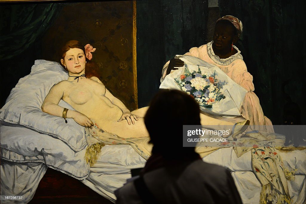 A woman looks at Edouard Manet's 'Olympia' on April 23, 2013 in Venice, during the 'Manet Return to Venice' exhibition, which runs until 18 August 2013, at the Doge's Palace in Venice. Edouard Manet's 'Olympia' will be appearing alongside the Titian's 'Venus of Urbino' a masterpice of Renaissance and source of ispiration for the French artist.