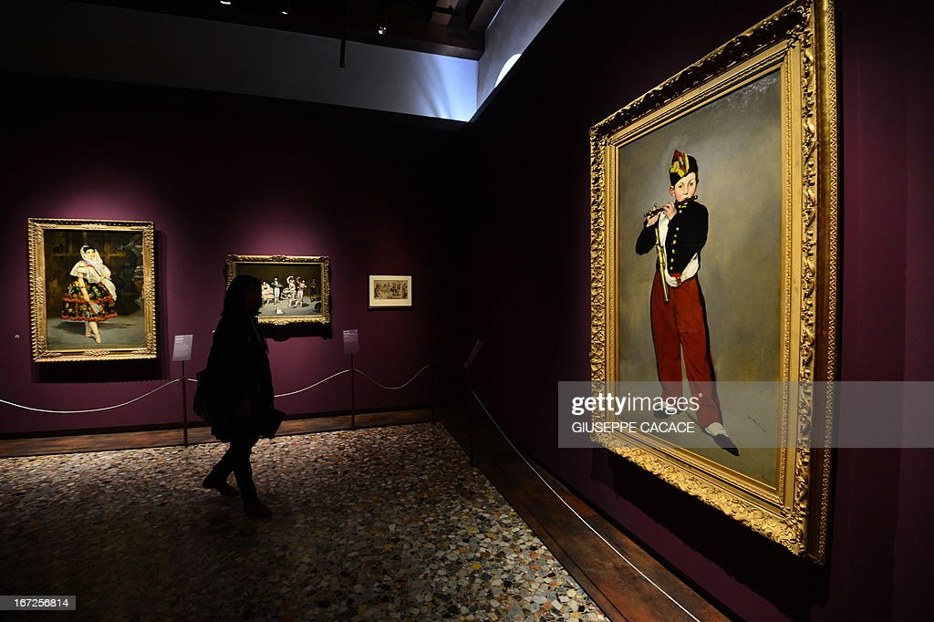 A woman looks at Edouard Manet's painting named Le fifre on April 23,2013 in Venice, during the 'Manet Return to Venice' exhibition, which runs until 18 August 2013, at the Doge's Palace in Venice. Edouard Manet's 'Olympia' will be appearing alongside the Titan's 'Venus of Urbino' a masterpice of Renaissance and source of ispiration for the French artist.