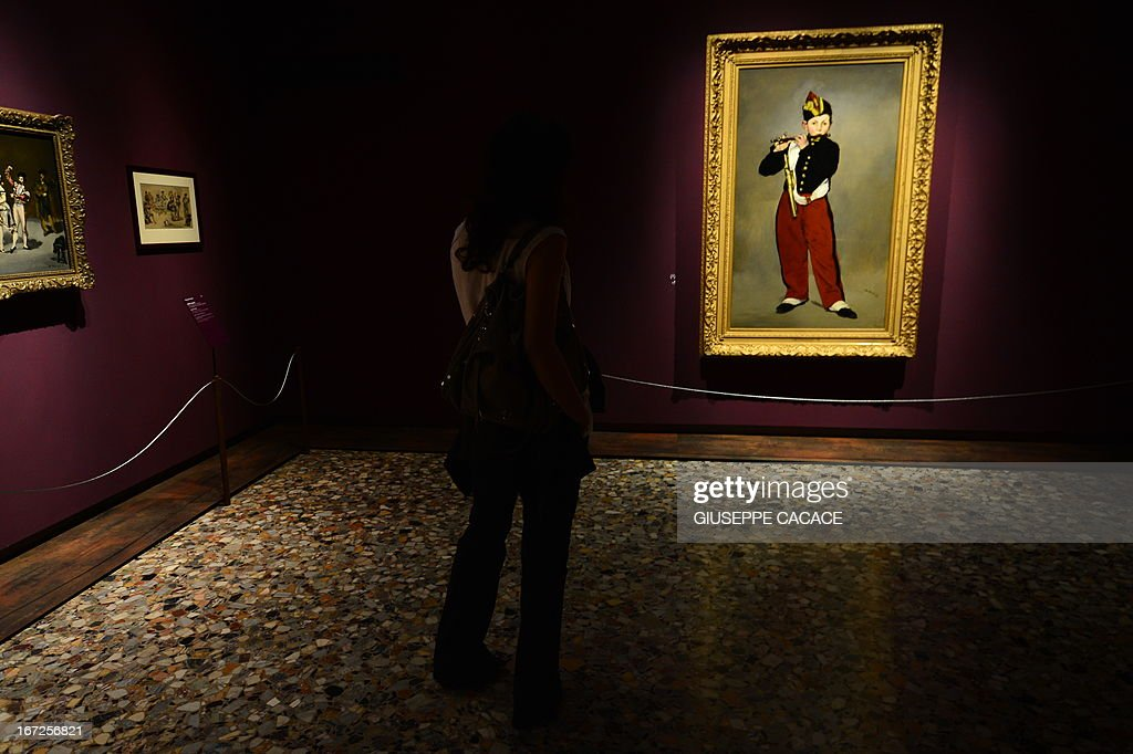 A woman looks at Edouard Manet's painting named Le fifre on April 23,2013 in Venice, during the 'Manet Return to Venice' exhibition, which runs until 18 August 2013, at the Doge's Palace in Venice. Edouard Manet's 'Olympia' will be appearing alongside the Titan's 'Venus of Urbino' a masterpice of Renaissance and source of ispiration for the French artist. AFP PHOTO / GIUSEPPE CACACE